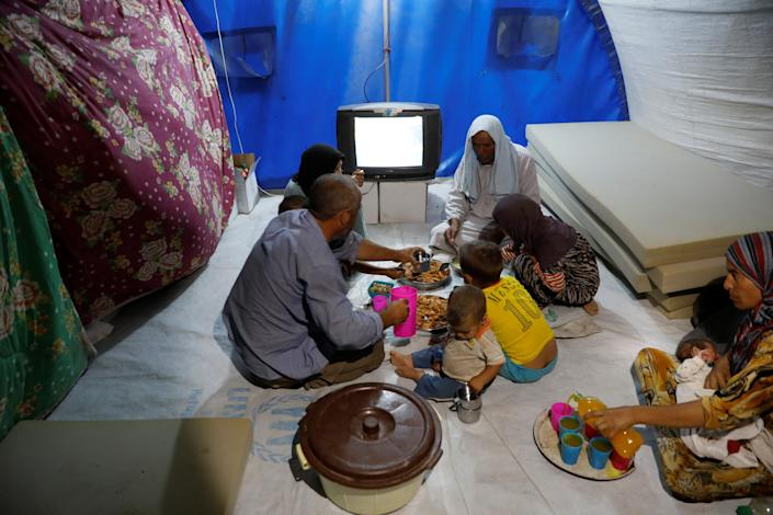 A displaced Iraqi family from Mosul eat a simple meal for their Iftar, during the Muslim holy month of Ramadan at a refugee camp al-Khazir in the outskirts of Erbil, Iraq June 10, 2017. Picture taken June 10, 2017. REUTERS/Erik De Castro