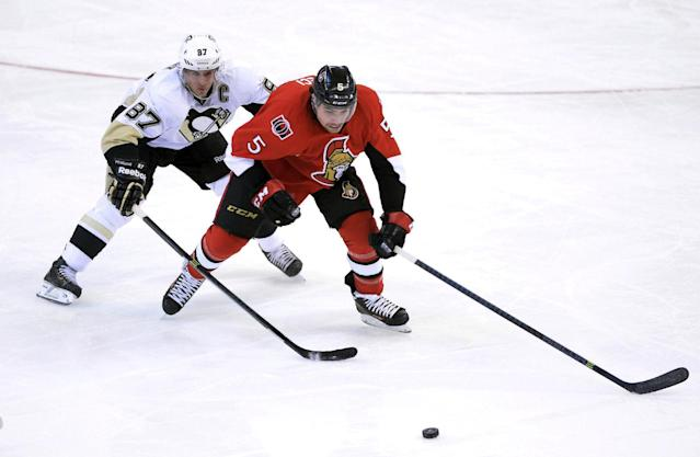 Ottawa Senators' Cody Ceci, right, keeps the puck away from Pittsburgh Penguins' Sidney Crosby during the first period of an NHL hockey game in Ottawa, Ontario on Monday, Dec. 23, 2013. (AP Photo/The Canadian Press, Sean Kilpatrick)