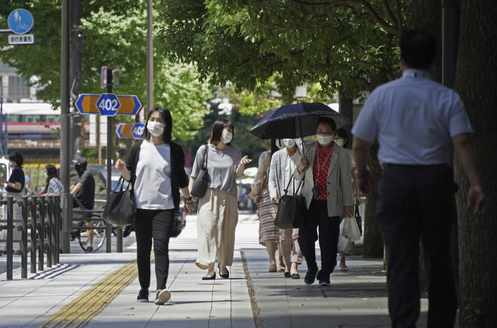 People wearing face masks to help curb the spread of the coronavirus cross an intersection in Tokyo Thursday, Aug. 5, 2021. Tokyo reported 5,042 new daily coronavirus cases on Thursday, hitting a record since the pandemic began as the infections surge in the Japanese capital hosting the Olympics. (AP Photo/Kantaro Komiya)
