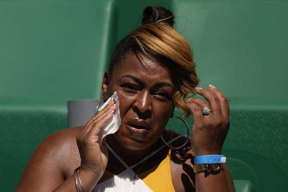 A spectator wipes her face to cool off at the U.S. Olympic Track and Field Trials Friday, June 25, 2021, in Eugene, Ore. (AP Photo/Charlie Riedel)