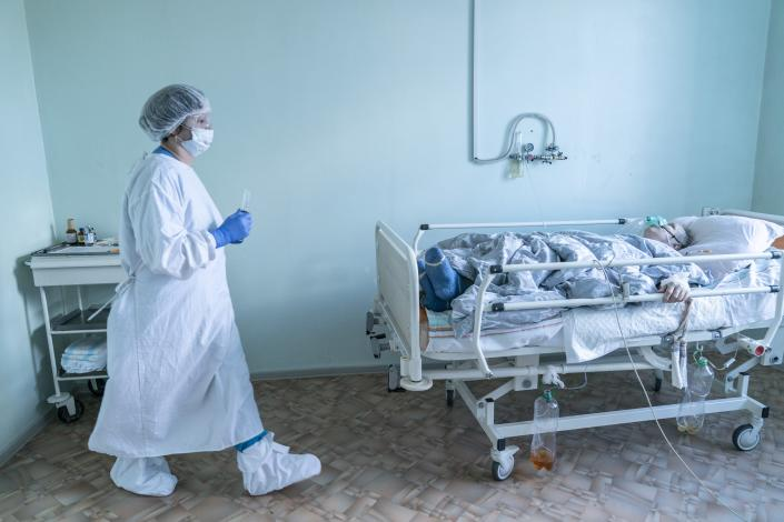 A nurse wearing a special suit against coronavirus walks to treat a patient with coronavirus at the intensive care unit at a hospital in the mining town of Selydove, 700 kilometers (420 miles) east of Kyiv, eastern Ukraine, Thursday, March 4, 2021. Ukraine received its first shipment of vaccine 500,000 AstraZeneca doses in late February. Yet, only about 19,000 people have been vaccinated since then. Ukrainians are becoming increasingly opposed to vaccination: an opinion poll this month by the Kyiv International Institute of Sociology found 60% of the country's people don't want to get vaccinated, up from 40% a month earlier. (AP Photo/Evgeniy Maloletka)
