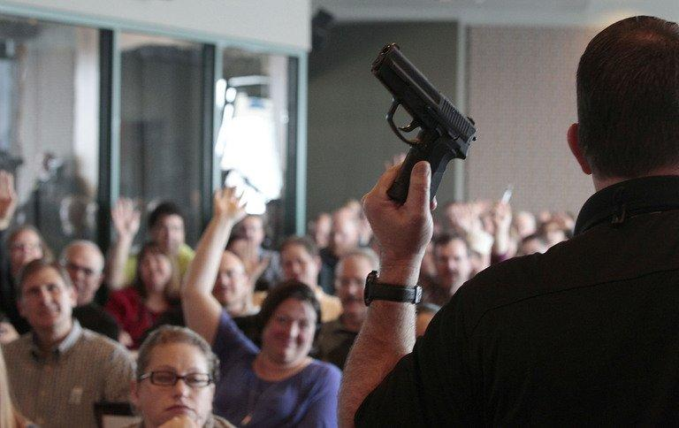 A firearms instructor holds a handgun up as he teaches a concealed-weapons training class to 200 Utah teachers on December 27, 2012 in West Valley City, Utah. Several US states are considering allowing school teachers to carry weapons, and educators, determined not to allow a repeat of the Newtown massacre, are flocking to training sessions