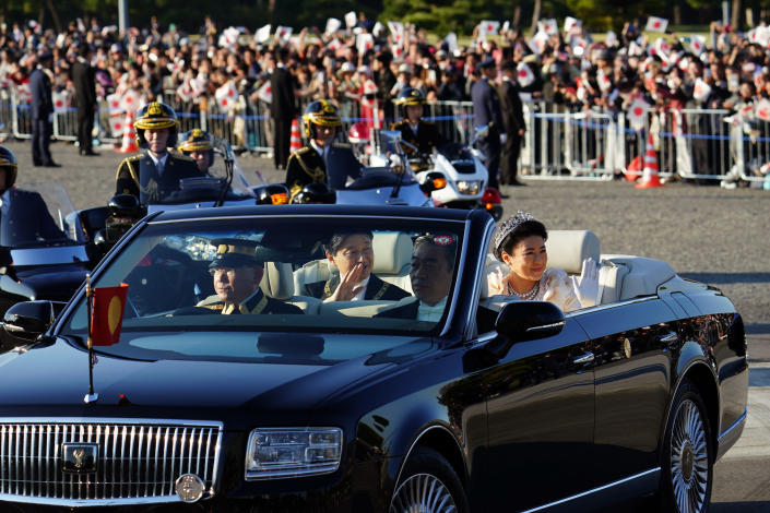 Japanese Emperor Naruhito, center, and Empress Masako, right, smiles during the royal motorcade in Tokyo, Sunday, Nov. 10, 2019.(AP Photo/Eugene Hoshiko)