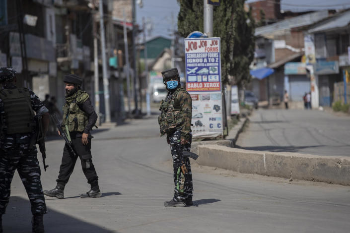 Indian paramilitary soldiers stand guard near the site of a shootout at Sopore, 55 kilometers (34 miles) north of Srinagar, Indian controlled Kashmir, Saturday, June 12, 2021. Two civilians and two police officials were killed in an armed clash in Indian-controlled Kashmir on Saturday, police said, triggering anti-India protests who accused the police of targeting the civilians. (AP Photo/Mukhtar Khan)
