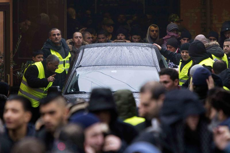 Mourners surround the hearse with Omar Abdel Hamid El-Hussein's body as it leaves the mosque on Dortheavej in Copenhagen, enroute to the Muslim cemetery in Broendby