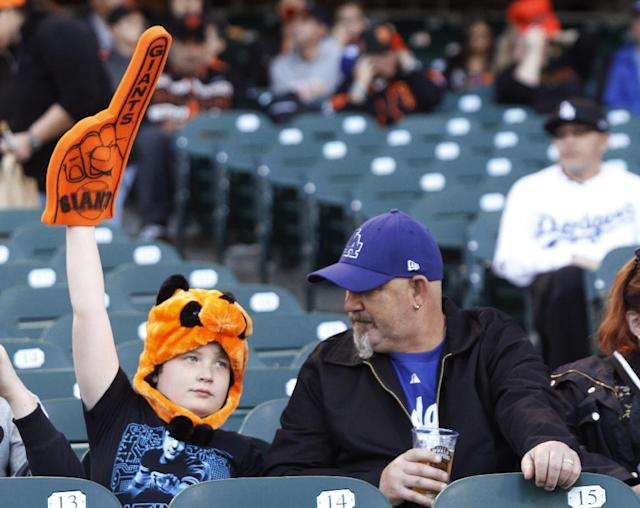 Benjamin Cust, left, and his father, Tony Cust, of Australia, wait for a baseball game between the San Francisco Giants and the Los Angeles Dodgers, Thursday, Sept. 26, 2013, in San Francisco. Benjamin is a Giants fan while his father is a Dodgers fan. (AP Photo/George Nikitin)
