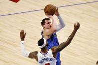Dallas Mavericks guard Luka Doncic, top, shoots a three-point basket in front of Los Angeles Clippers forward Marcus Morris Sr., bottom, in the first half during Game 6 of an NBA basketball first-round playoff series in Dallas, Friday, June 4, 2021. (AP Photo/Michael Ainsworth)