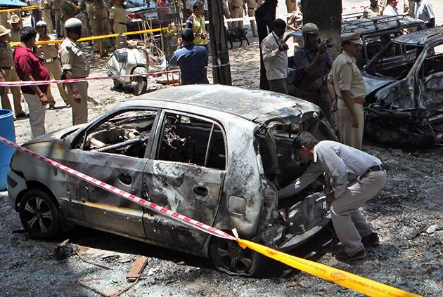 An Investigator looks for evidence inside a charred vehicle following a blast near the Bharatiya Janata Party (BJP) office in Bangalore on April 17, 2013. Police in the southern city of Bangalore said Wednesday they were investigating a minor blast outside the office of a political party which injured 12 people.