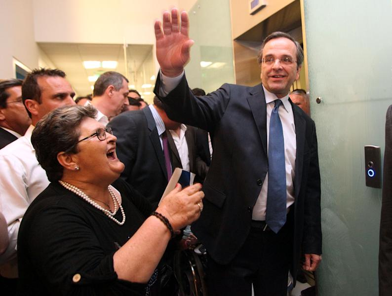 Greece's conservative leader of New Democracy Antonis Samaras waves to his supporters at the headquarters of his party in Athens, Sunday, May 6, 2012. Samaras called for a coalition government with two aims, for Greece to remain in the euro and to amend the terms of its international bailout. (AP Photo/Eurokinissi, Giannis Panagopoulos) GREECE OUT