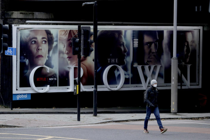 FILE - In this Friday, Nov. 20, 2020 file photo, a man wearing a face mask in London, walks past a billboard advertising 'The Crown' television series about Britain's Queen Elizabeth II and the royal family. Britain's royal family and television have a complicated relationship. The medium has helped define the modern monarchy: The 1953 coronation of Queen Elizabeth II was Britain's first mass TV spectacle. Since then, rare interviews have given a glimpse behind palace curtains at the all-too-human family within. (AP Photo/Matt Dunham, File)