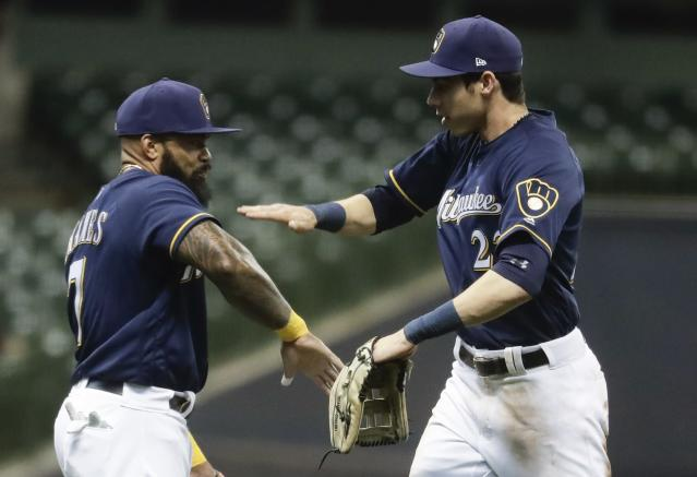 Milwaukee Brewers' Christian Yelich and Eric Thames celebrate after a baseball game against the Cincinnati Reds Wednesday, April 18, 2018, in Milwaukee. The Brewers won 2-0. (AP Photo/Morry Gash)
