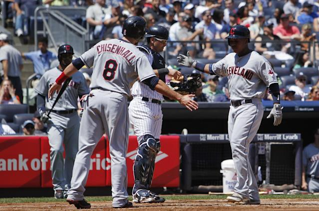 Cleveland Indians' Lonnie Chisenhall, left, congratulates teammate Jose Ramirez at home plate after Chisenhall scored on a two-run home run by Ramirez during the second inning of a baseball game against the New York Yankees, Saturday, Aug. 9, 2014, in New York. (AP Photo/Jason DeCrow)