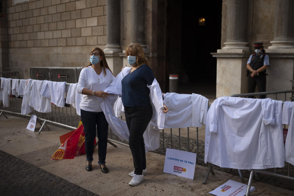 Health workers remove their doctor coats in front of the Palace of the Generalitat, the headquarter of the Government of Catalonia, as they take part in a protest against their working conditions in Barcelona, Spain, Thursday, Oct. 29, 2020. As more of Spain's regions apply border transit restrictions, the government is seeking parliamentary approval to extend the country's newly declared state of emergency to rein in the resurging coronavirus pandemic until May, a proposal that is rejected by some opposition parties. (AP Photo/Emilio Morenatti)