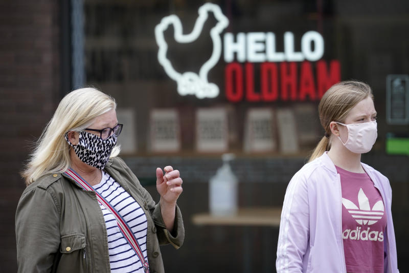 OLDHAM, ENGLAND - JULY 29: People wear face masks as they go about their daily lives Oldham on July 29, 2020 in Oldham, England. Oldham Council is taking preventative measures to prevent a local lockdown during the coronavirus pandemic. The Greater Manchester town has become England's second highest Covid-19 infection rate, after Blackburn with Darwen, and is currently showing a Covid-19 infection rate of 54.3 cases per 100,000 people. (Photo by Christopher Furlong/Getty Images)