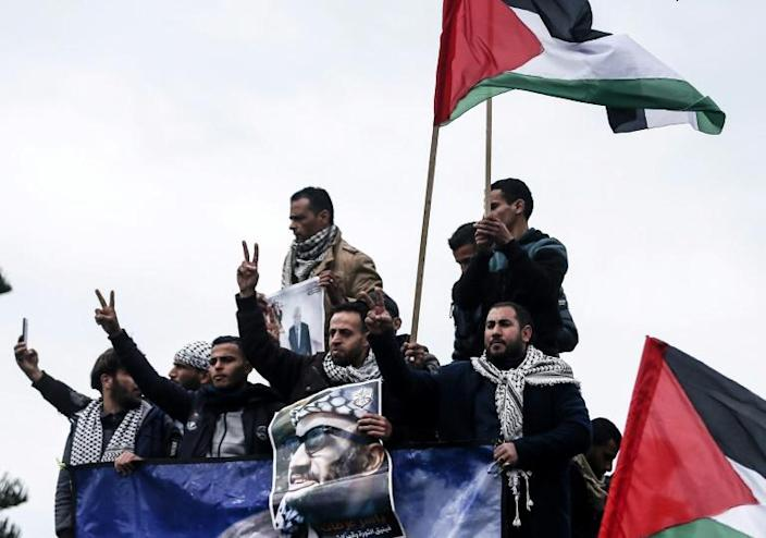 Palestinian protesters in Gaza City hold up portraits of president Mahmud Abbas and late Palestinian leader Yasser Arafat ahead of Abbas' appearance at the UN Security Council (AFP Photo/MAHMUD HAMS)
