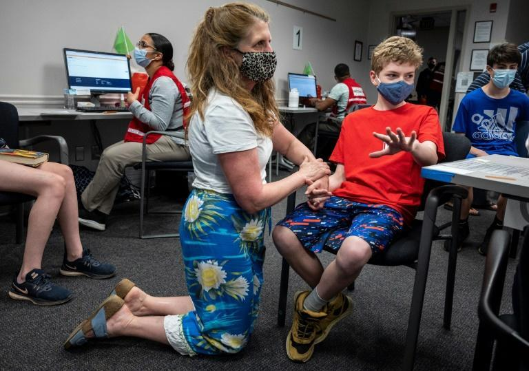 Elizabeth Brauer (C) holds the hand of her son Luke Brauer, 13, before he receives a Covid-19 vaccination at the Fairfax Government Center vaccination clinic in Fairfax, Virginia