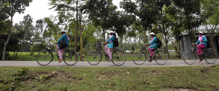 """In this Sept. 30, 2012, photo, Bangladeshi Info Ladies pedal their way from one place to another at Saghata, a remote impoverished farming village in Gaibandha district, 120 miles (192 kilometers) north of capital Dhaka, Bangladesh. Dozens of """"Info Ladies"""" bike into remote Bangladeshi villages with laptops and Internet connections, helping tens of thousands of people - especially women - get everything from government services to chats with distant loved ones. (AP Photo/A.M. Ahad)"""