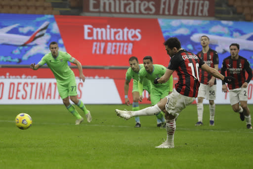 AC Milan's Hakan Calhanoglu scores with penalty against Lazio during a Serie A soccer match between AC Milan and Lazio, at the San Siro stadium in Milan, Italy, Wednesday, Dec. 23, 2020. (AP Photo/Luca Bruno)