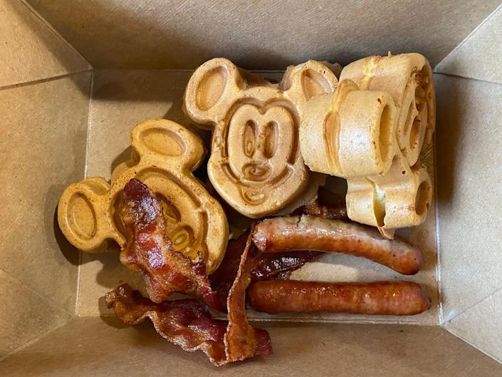 Mickey Mouse waffles with sides of bacon and sausage in 2021.