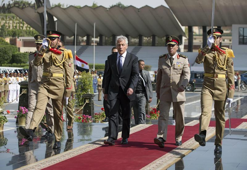 U.S. Secretary of Defense Chuck Hagel, center, arrives with an Egyptian army official to lay a wreath at the Tomb of the Unknown Soldier and the tomb of late president Anwar al-Sadat in Cairo on Wednesday, April 24, 2013. By including Cairo on his first Mideast tour as defense secretary, Chuck Hagel is highlighting the Obama administration's hope of preserving influence with the Egyptian military as the country struggles with its transition to democracy.(AP Photo/Jim Watson, Pool)