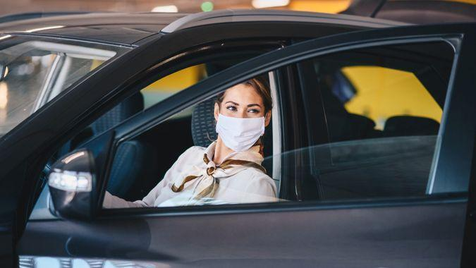 Young attractive elegant businesswoman with protective face mask on exiting car during corona virus outbreak.