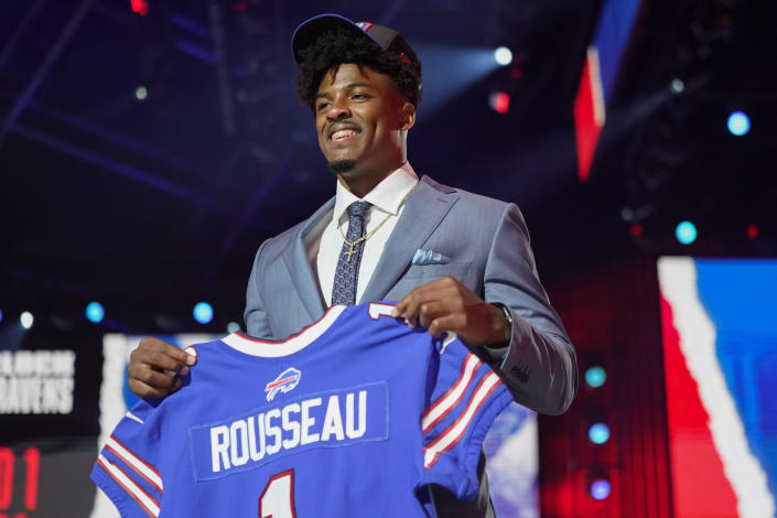 FILE - In this Thursday April 29, 2021, file photo, The Buffalo Bills' top draft pick, Gregory Rousseau holds up a jersey after he was selected in the first round of the NFL football draft in Cleveland. Buffalo opened the draft by selecting edge rushers, Miami's Greg Rousseau and Wake Forest's Carlos Basham, with their first two picks, and then taking Northern Iowa offensive tackle Spencer Brown in the third round on Friday. (AP Photo/Tony Dejak, File)