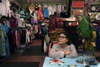 """Martha Medina, owner of Olveritas souvenir shop on Olvera Street, sits for a photo in her shop in Los Angeles, Friday, June 4, 2021. During the darkest days of the coronavirus pandemic, Medina would return to her shuttered store on Los Angeles' oldest street to make sure everything was securely in place. Missing were the customers, employees and the constant pulse of traditional Mexican music such as cumbia, boleros and sones Jarochos, the Veracruz sound. """"Those days I felt very sad,"""" Medina said. """"I had the feeling I would never open the shop again."""" (AP Photo/Jae C. Hong)"""