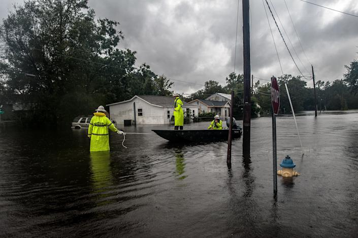 Workers with Duke Energy move through Lumberton, North Carolina, by boat in attempts to restore power to customers on Sunday after intense flooding in the town. (Photo: Joseph Rushmore for HuffPost)