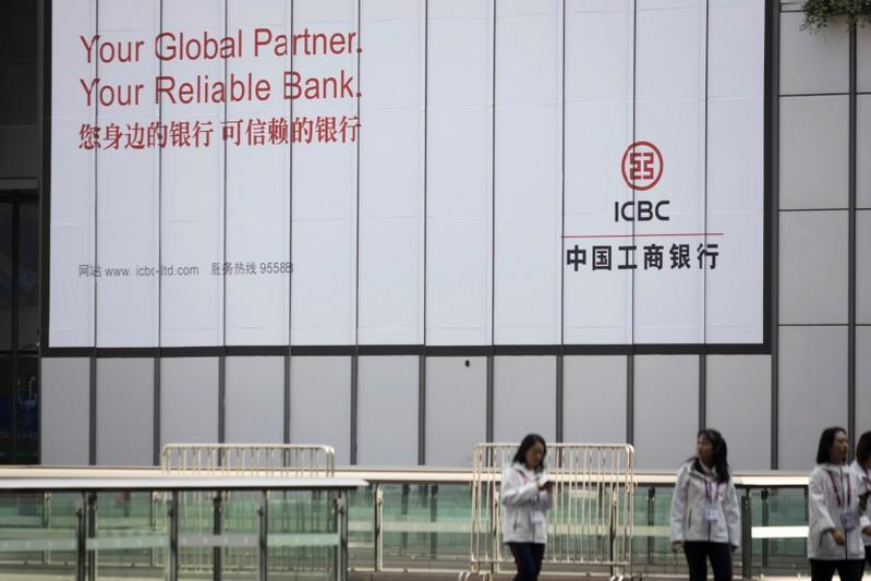 People walk past a sign of the Industrial and ICBC at the venue for the second China International Import Expo (CIIE) in Shanghai
