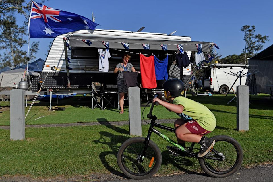 Holiday maker Debbie Coates in Lake Conjola, NSW, stands outside a caravan as a boy cycles past.