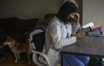 Natty Jumreornvong, a Thai-born medical student at the Icahn School of Medicine at Mount Sinai, reads a tablet after arriving home, Thursday April 29, 2021, in New York. Jumreornvong, a victim of anti-Asian attacks, is among medical professionals of Asian and Pacific Island descent who feel the anguish of being racially targeted because of the virus while toiling to keep people from dying of it. (AP Photo/Bebeto Matthews)