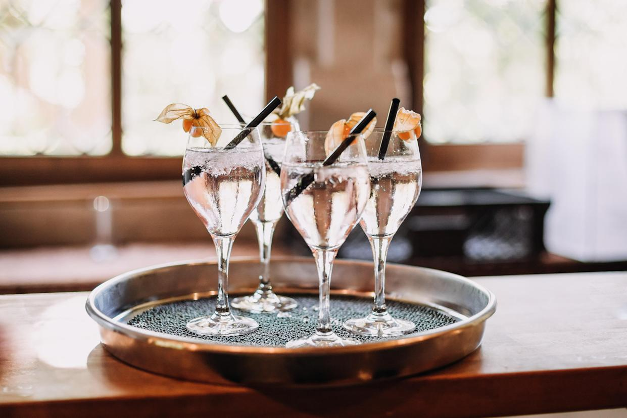 four clinking champagne glasses with transparent sparkling spritzer, Weinschorle on tray salver at a summer wedding party