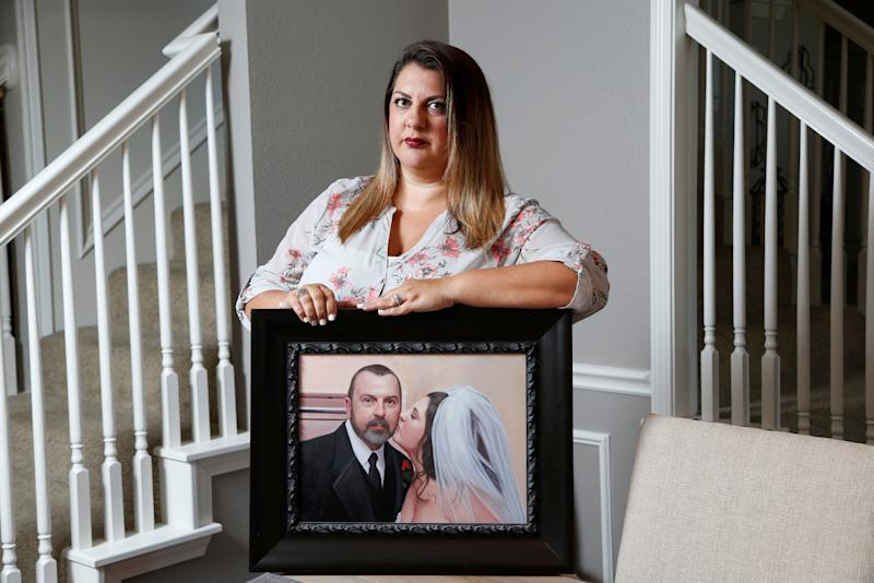 Farrah Fasold poses for a portrait with a painting of her late father Harold Dillard at her home in Flower Mound, Texas, U.S. July 18, 2017. Picture taken July 18, 2017. To match Special Report USA-BODIES/BROKERS REUTERS/Brandon Wade