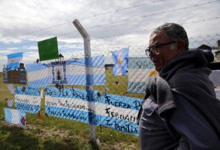 Ricardo Coronel, father of Victor Coronel, one of the 44 crew members of the missing at sea ARA San Juan submarine, stands next to signs in support of the crew outside an Argentine naval base in Mar del Plata, Argentina November 22, 2017. REUTERS/Marcos Brindicci