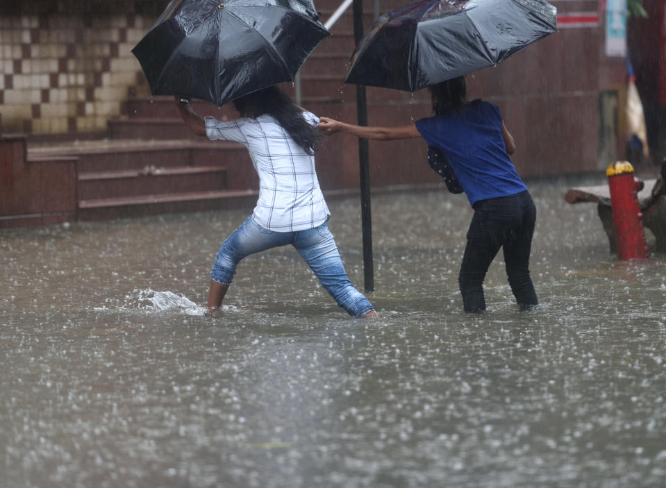 People cross the waterlogged street during heavy rain at Hindmata, Parel, on July 16, 2020 in Mumbai, India. (Photo by Satish Bate/Hindustan Times via Getty Images)