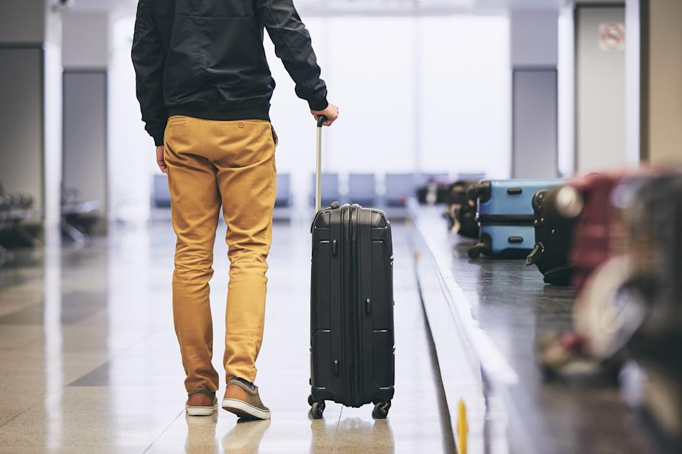Low Section Of Young Man With Luggage Standing By Conveyor Belt At Airport