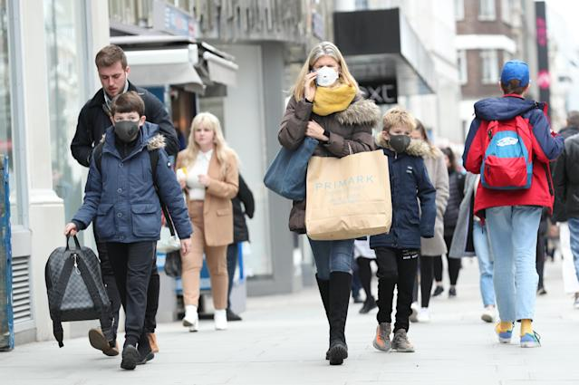 A woman wearing a protective face mask walking down Oxford Street in London, as the Government's top scientist warned that up to 10,000 people in the UK are already infected. (Getty Images)