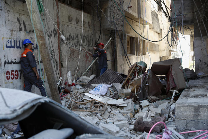 Workers inspect the rubble of the destroyed Abu Hussein building that was hit by an Israeli airstrike early morning, in Gaza City, Wednesday, May 19, 2021. (AP Photo/Adel Hana)