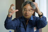 In this Oct. 22, 2012 photo, Yuichi Okamura, manager of the Water Treatment System Department at the Fukushima Dai-ichi nuclear power plant, gestures while speaking during an exclusive interview at the Tokyo Electric Power Co. (TEPCO) headquarters in Tokyo. As the March 11, 2011 disaster unfolded, Okamura - first in Tokyo and later in Fukushima - was among those who feverishly devised emergency steps to inject water into the overheating reactors and spent fuel pools to bring the plant under tenuous control. He was tasked with tackling the problem of radioactive water leak and setting up a treatment system that would decontaminate the water to reduce health risks for workers and environmental damage in case it spilled out. (AP Photo/Shizuo Kambayashi)