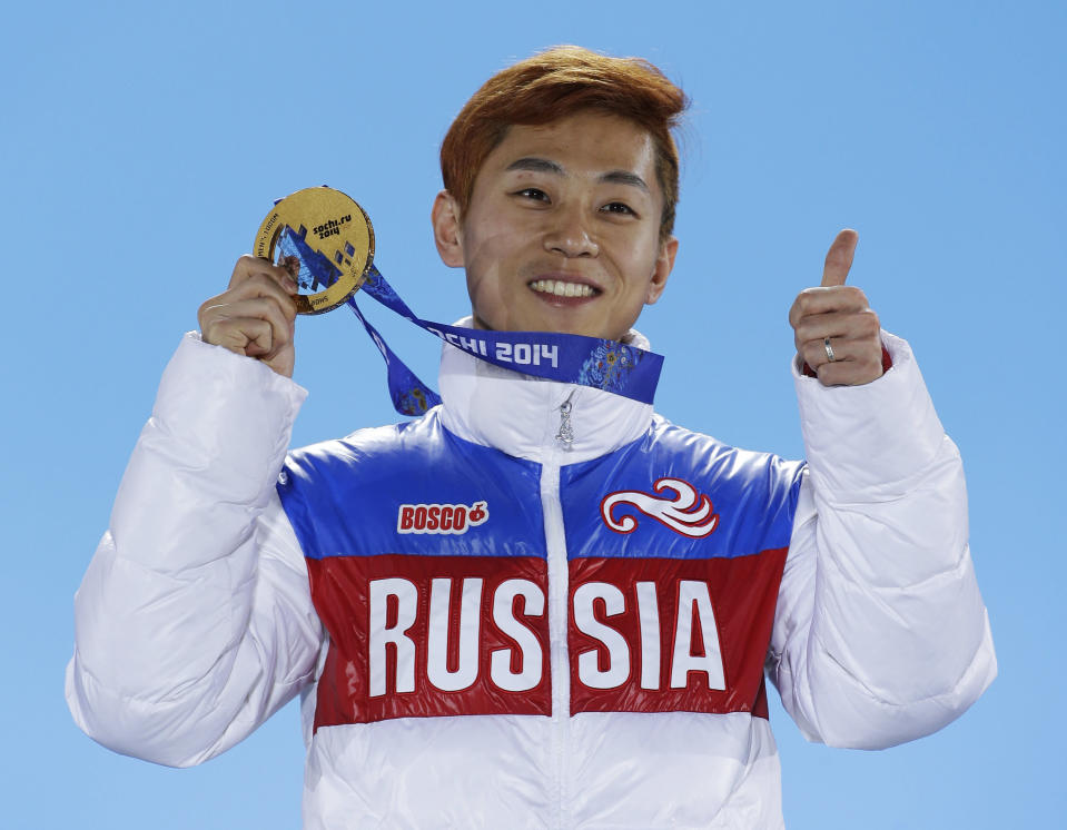 Viktor Ahn, of Russia, gestures while holding his medal during the medals ceremony at the Winter Olympics in Sochi, Russia. (AP)