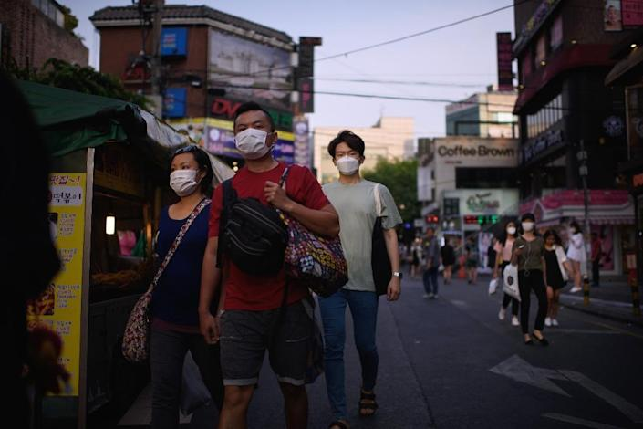 People with face masks are seen on a street in Seoul, on June 9, 2015 (AFP Photo/Ed Jones)