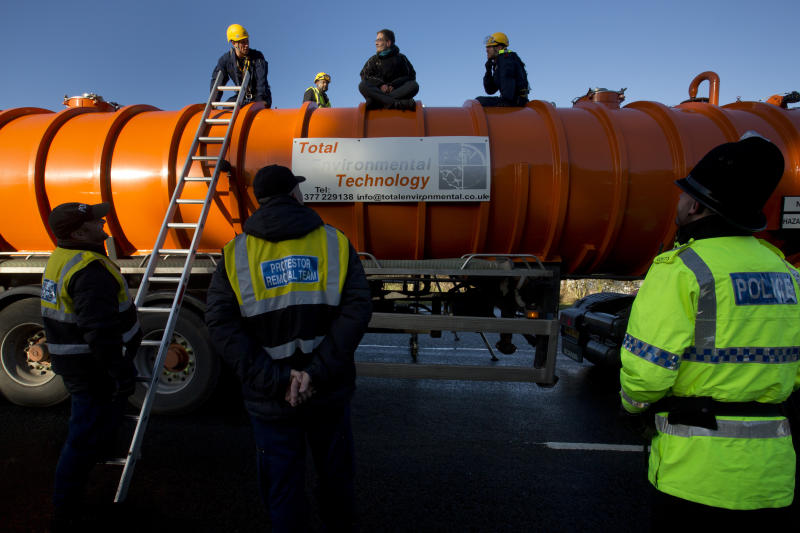FILE - In this Monday, Jan. 13, 2014 file photo, police prepare to remove a protestor from the top of a vehicle waiting to enter an exploratory drill site for the controversial gas extraction process known as fracking at Barton Moss in Manchester, England. The British government announced Saturday Nov. 2, 2019, that it will no longer allow fracking because of new scientific analysis that casts doubts on the safety of the controversial practice, but some critics said the measure falls short because it is not a permanent ban. (AP Photo/Jon Super, File)