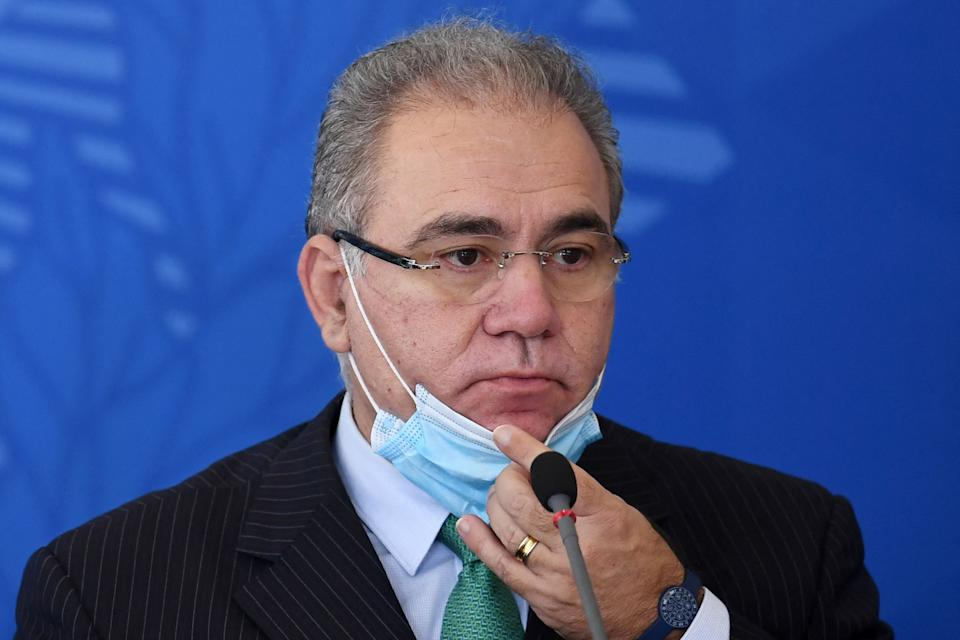 Brazilian Health Minister Marcelo Queiroga takes off his face mask during a press conference, after a meeting of the Covid-19 National Coordination Committee to Combat the Pandemic with Brazilian President Jair Bolsonaro at the Planalto Palace in Brasilia, on April 14, 2021. - In the midst of the biggest crisis caused by the uncontrolled pandemic of the new coronavirus, the Brazilian government is looking for solutions to reduce the number of people infected and killed by the COVID-19. (Photo by EVARISTO SA / AFP) (Photo by EVARISTO SA/AFP via Getty Images)