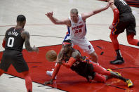 Portland Trail Blazers forward Robert Covington, center, passes the ball to guard Damian Lillard, left, as Detroit Pistons center Mason Plumlee defends during the first half of an NBA basketball game in Portland, Ore., Saturday, April 10, 2021. (AP Photo/Steve Dykes)