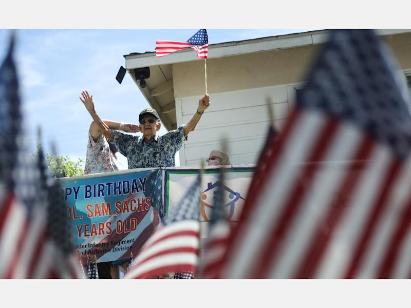U.S. Army World War II veteran Lt. Colonel Sam Sachs, who turned 105 Sunday, holds an American flag at his drive-by birthday party amid the coronavirus pandemic on April 26 in Lakewood, Callifornia.