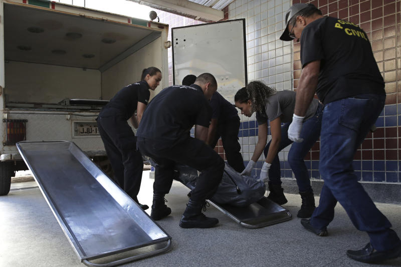 Agents of the criminal police carry a black bag with the body of Debora Tereza Correia, murdered today by her boyfriend at the city education department in Brasilia, Brazil, Monday, May 20, 2019. Brazilian officials say a police officer shot his ex-girlfriend to death in her office at the city education department in Brazil's capital and then killed himself. Forty-three-year-old Debora Tereza Correia was shot three times and died immediately. (AP Photo/Eraldo Peres)