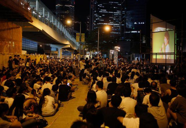 Over a thousand protesters listen to a 14-year-old secondary school student speaking on a podium, shown on a screen, during a rally in Hong Kong September 26, 2014.