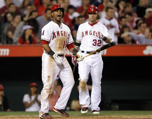 Los Angeles Angels' Luis Jimenez, left, yells out to congratulate Angels designated hitter Albert Pujols (not pictured) for hitting in Jimenez on a single in the seventh inning against the Detroit Tigers during a baseball game Friday, April 19, 2013, in Anaheim. Angels' Josh Hamilton (32) is the on deck batter looking on. (AP Photo/Alex Gallardo)