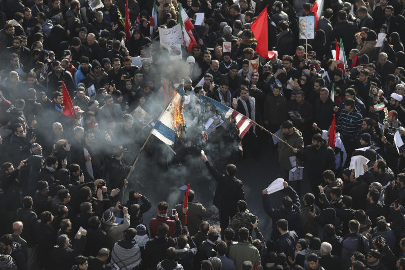 Mourners burn mock flags of the U.S. and Israel during a funeral ceremony for Iranian Gen. Qassem Soleimani and his comrades, who were killed in Iraq in a U.S. drone strike on Friday, at the Enqelab-e-Eslami (Islamic Revolution) square in Tehran, Iran, Monday, Jan. 6, 2020. (AP Photo/Ebrahim Noroozi)