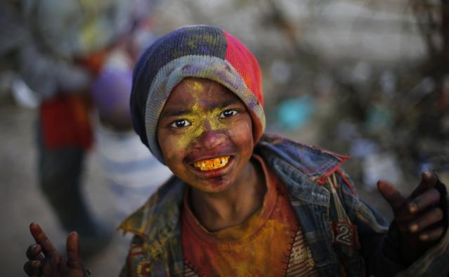 A boy reacts to the camera as he celebrates 'Holi', India's festival of colours, outside his makeshift home in New Delhi March 14, 2014. REUTERS/Adnan Abidi (INDIA - Tags: SOCIETY PORTRAIT TPX IMAGES OF THE DAY)